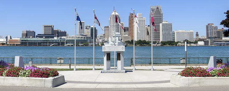 Monument with granite, plaques, and flags in a riverfront park.