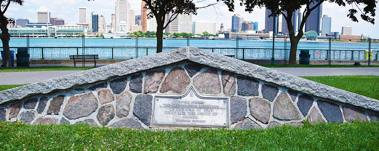 Bronze plaque mounted in masonry in a riverfront park.