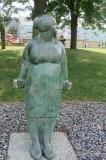 Bronze sculpture of a lady standing, leaning on a horizontal bar, looking off into the distance.