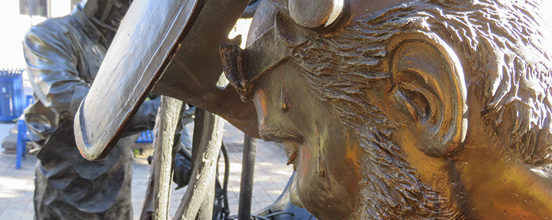 Detail of a bronze sculpture of an auto worker at work.