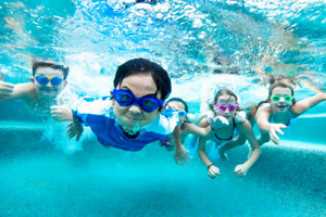 Underwater view of children diving into water