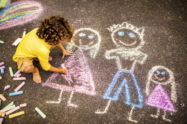 Child drawing family with chalk