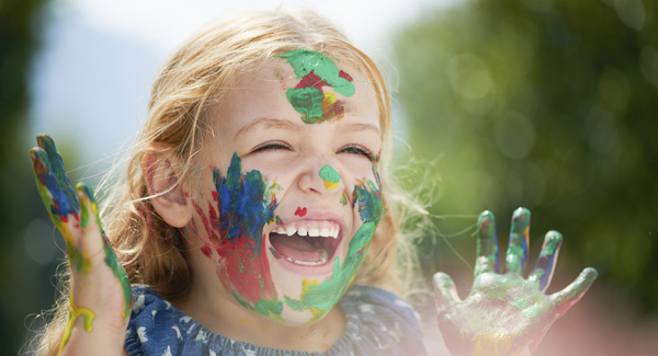Laughing girl with face and hands covered in paint